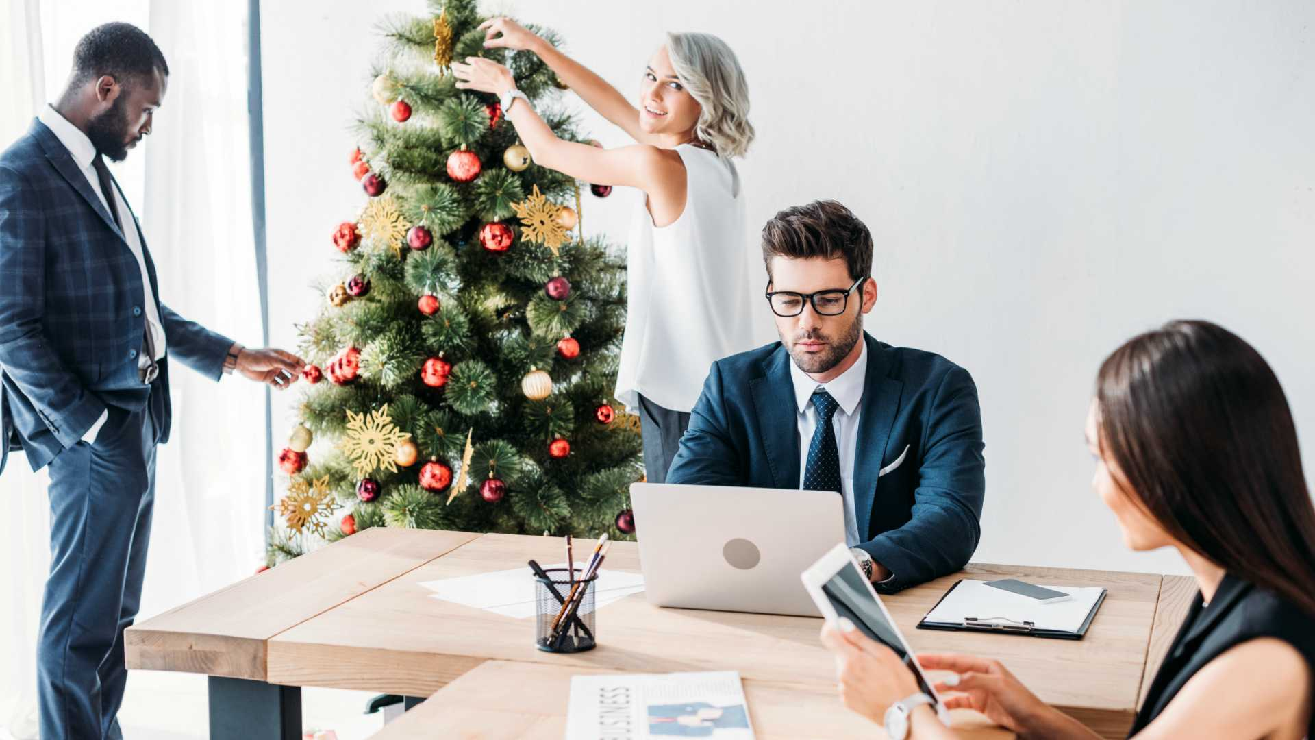 employees working and decorating a Christmas tree in an open office